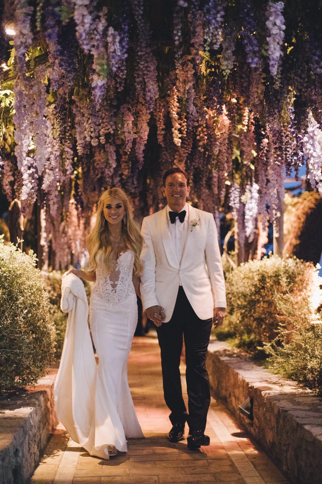 the bride and the groom walking hand in hand under the wisteria