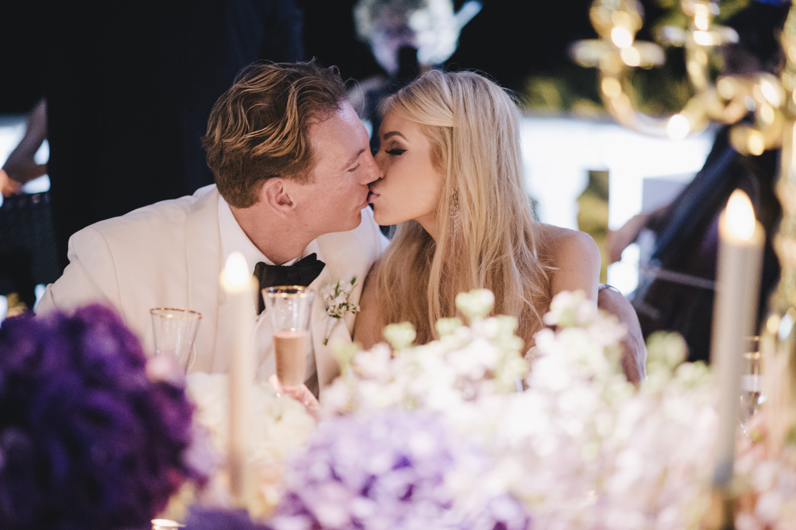 the groom kisses the bride at the wedding table