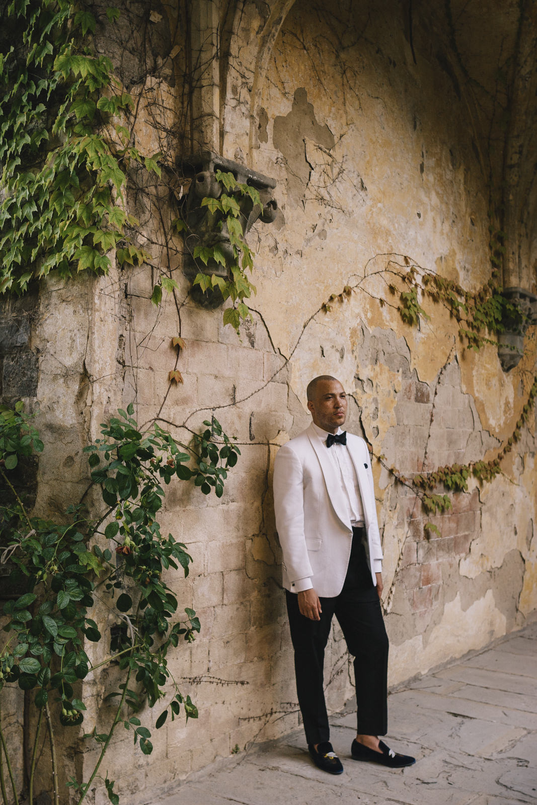 groom's portrait lining against a wall