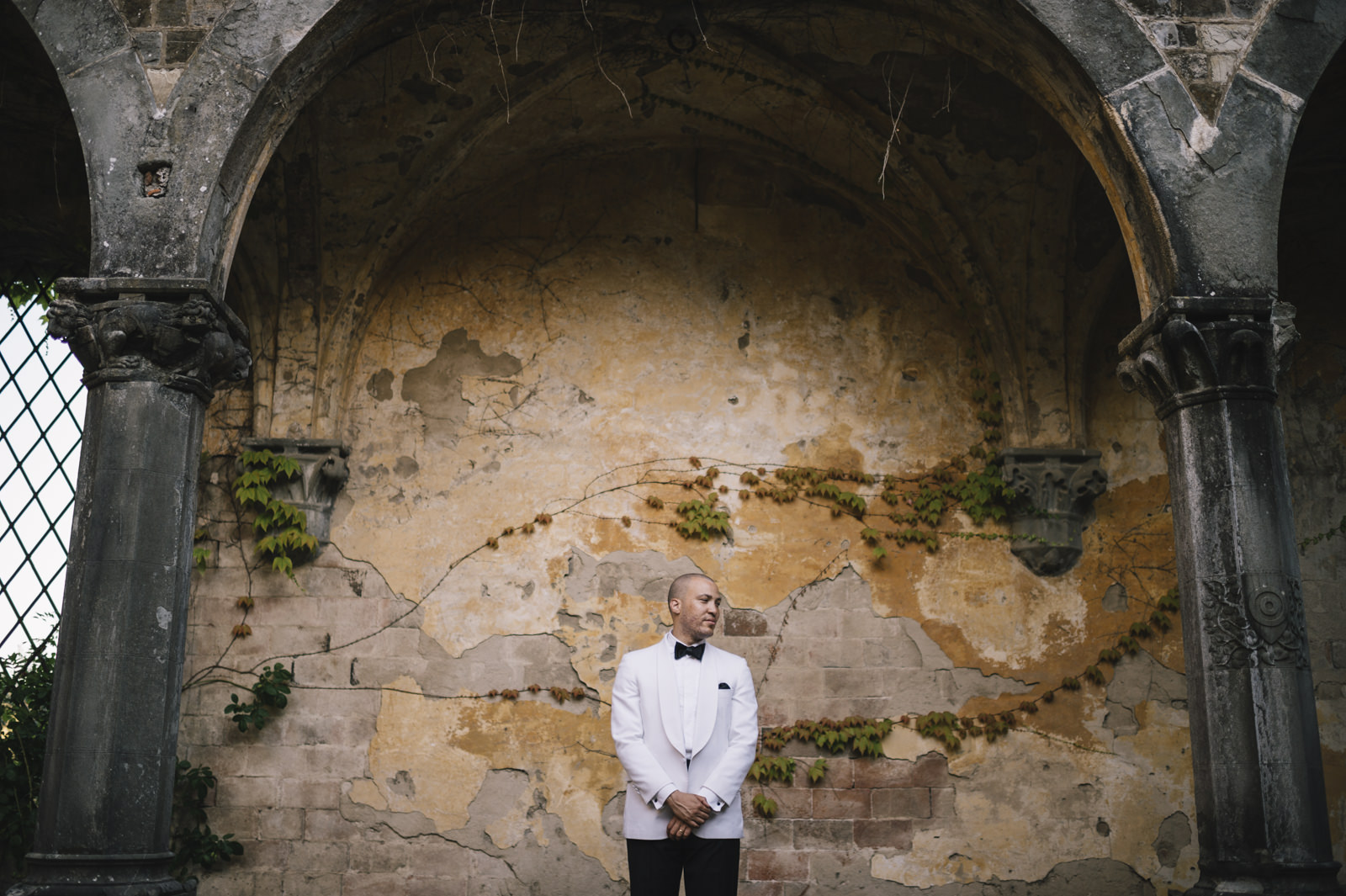 groom's portrait against a brown ancient wall