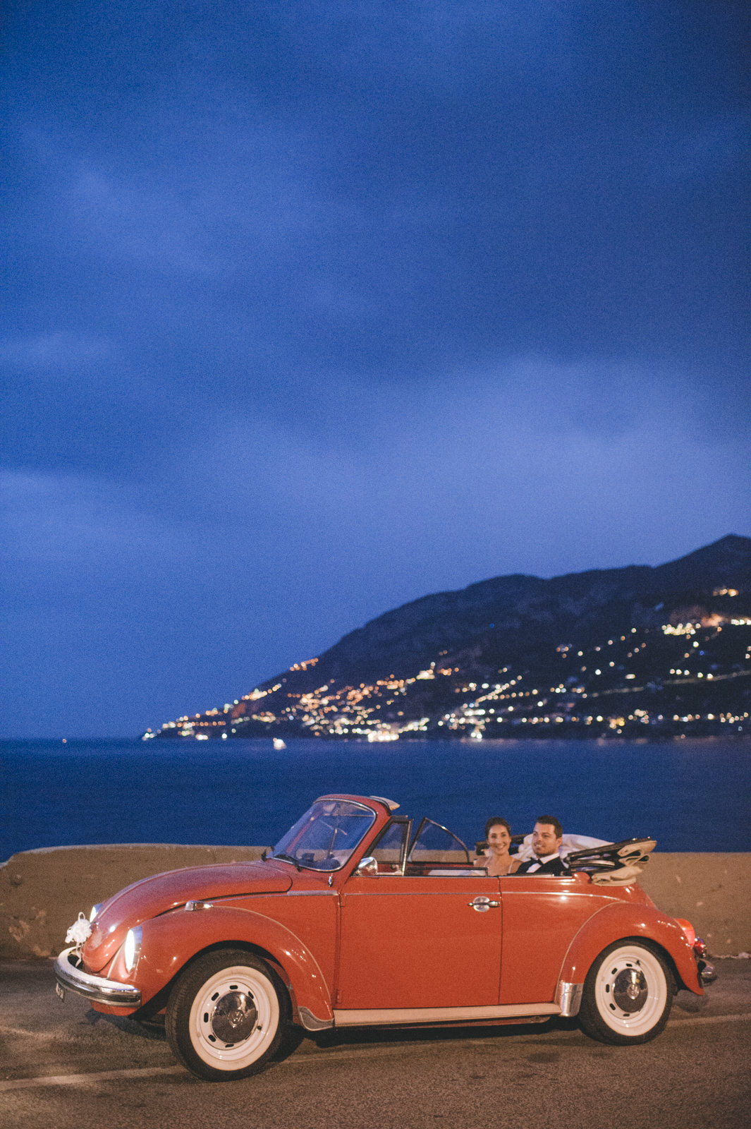 the bride and the groom sitting in their red wedding car with the amalfi coast on the background