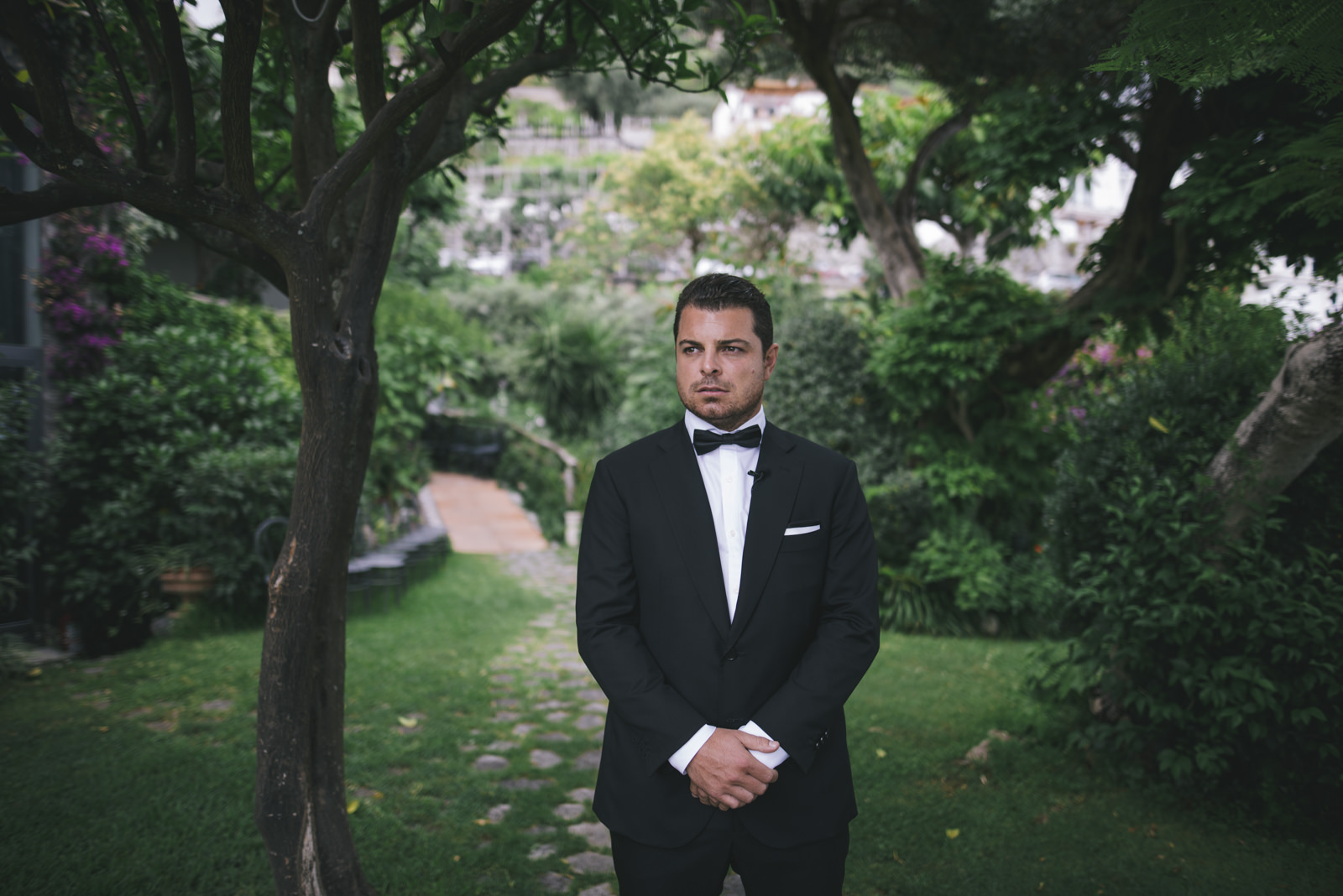 the groom standing in the garden of the hotel santa caterina and waiting for the arrival of the bride