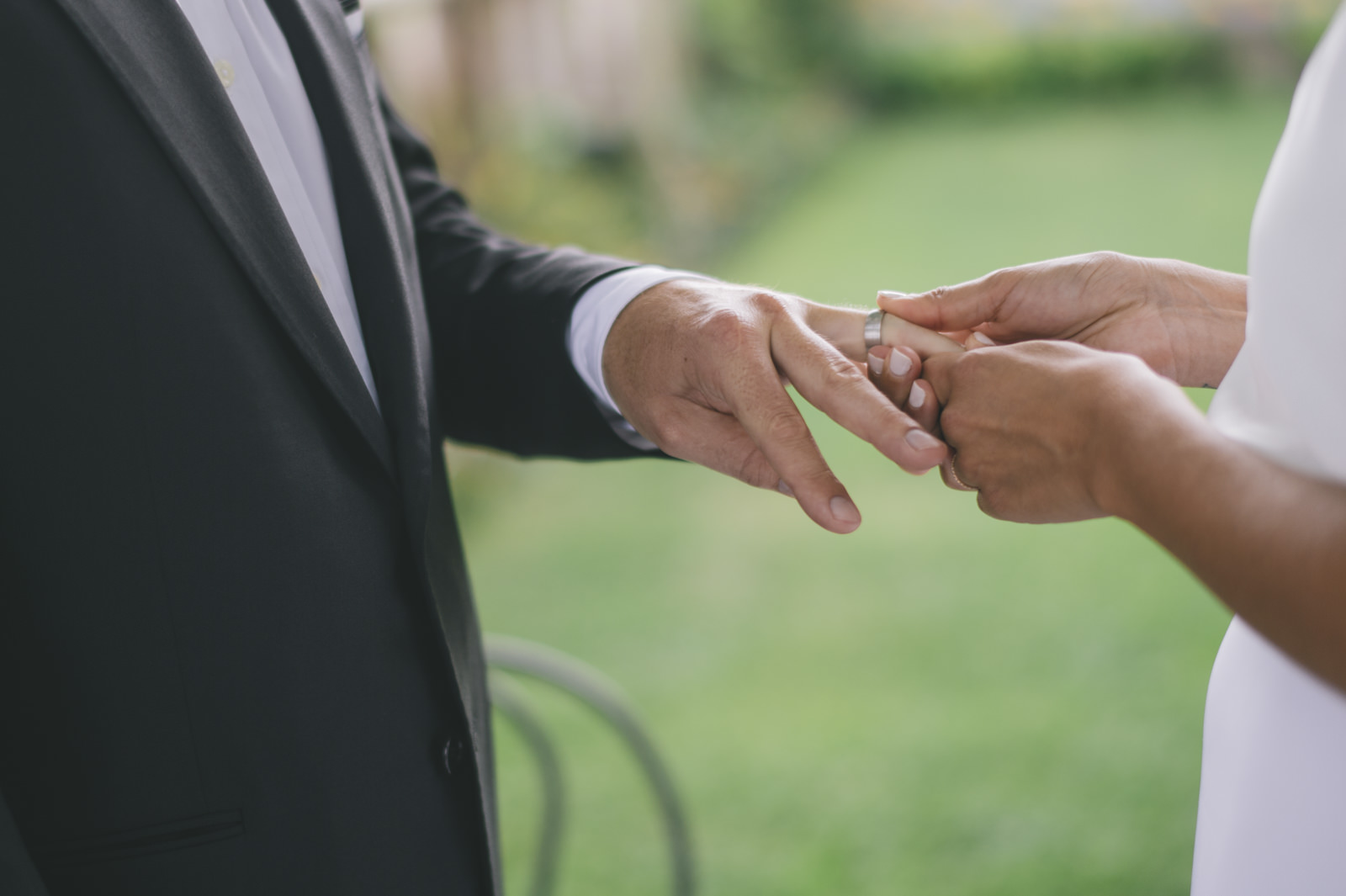 close up of the bride and groom's hands during the exchange of rings
