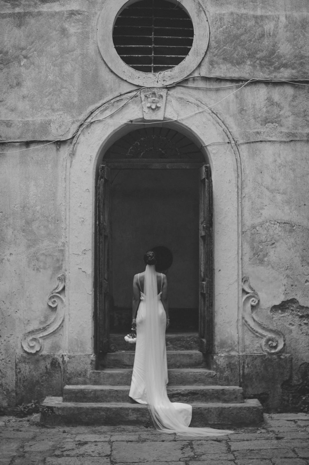 black and white portrait of the bride standing in a typical old Italian courtyard