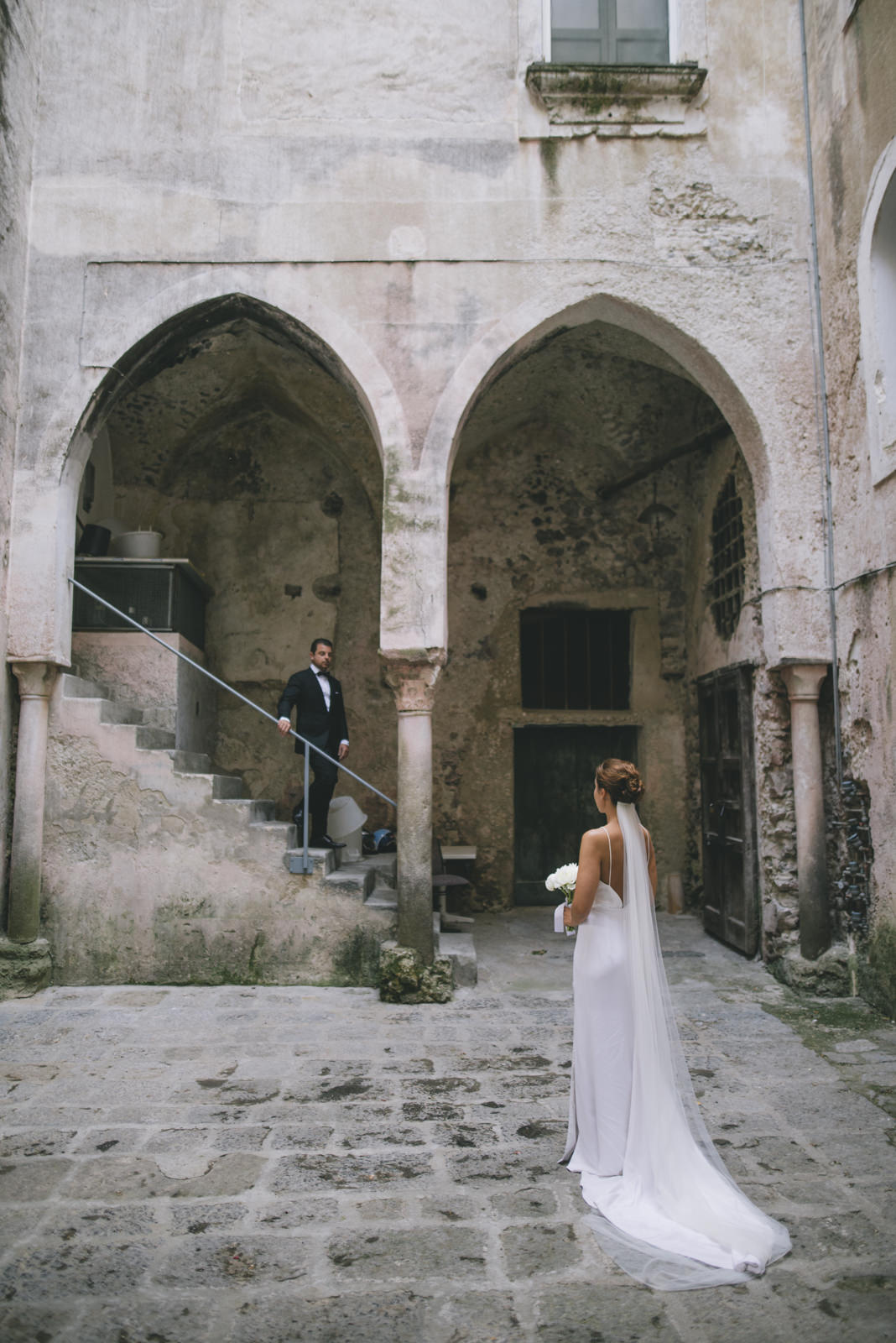 the bride and the groom standing in a typical old Italian courtyard