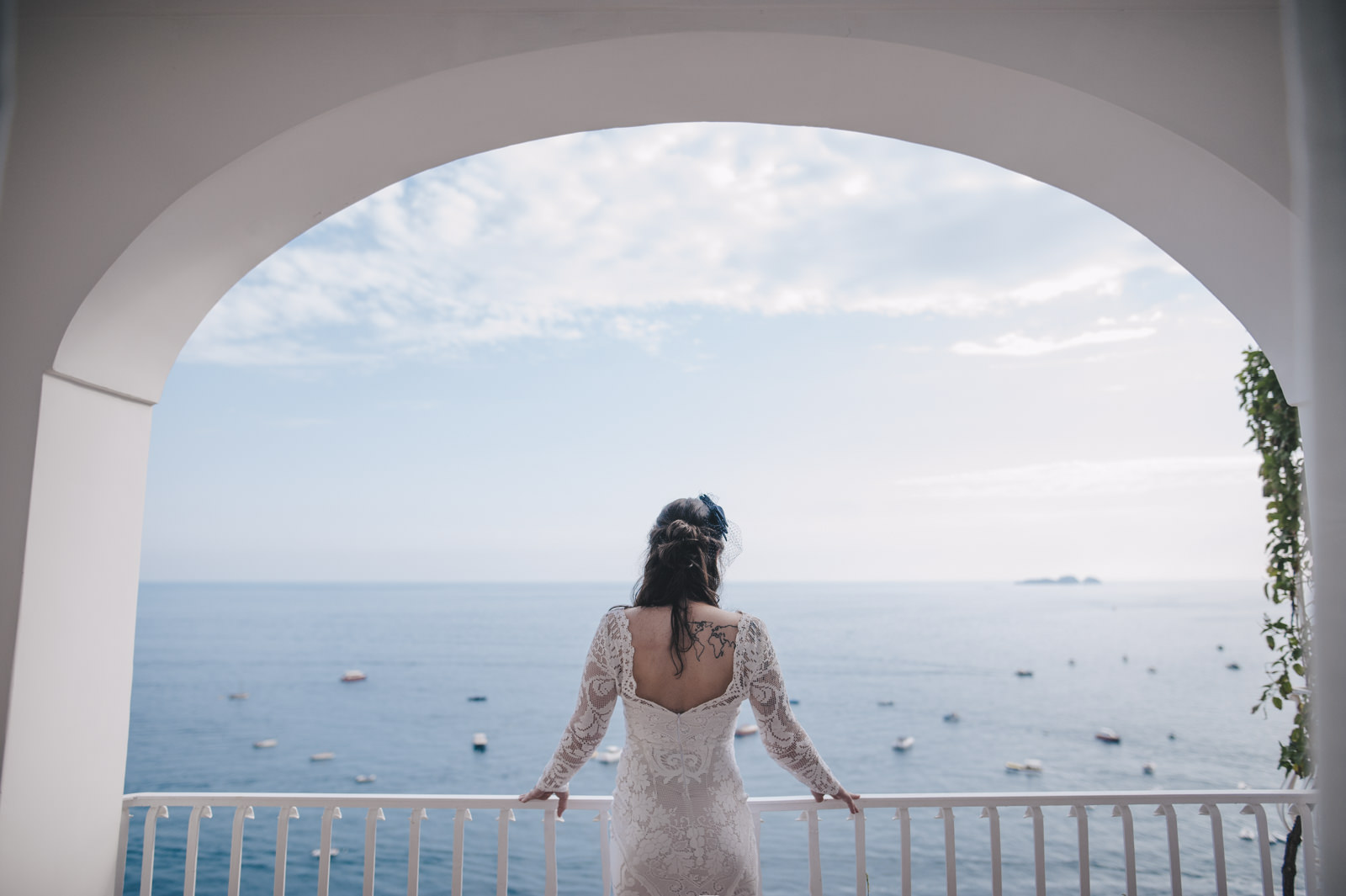 the bride on a balcony looking at the sea