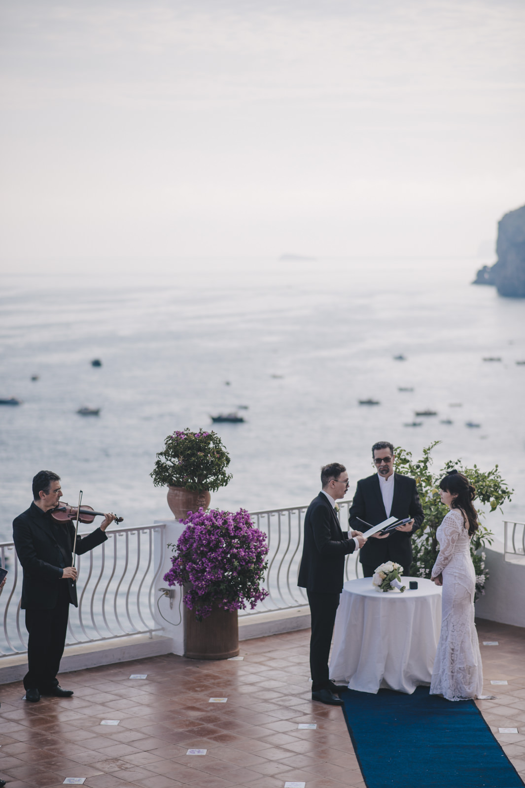 moment of the wedding ceremony on a terrace at the hotel Marincanto with the couple, the celebrant and the Violinist