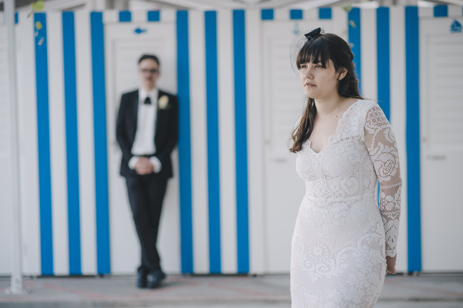 bride and groom's portrait with a white and light blue wall as background