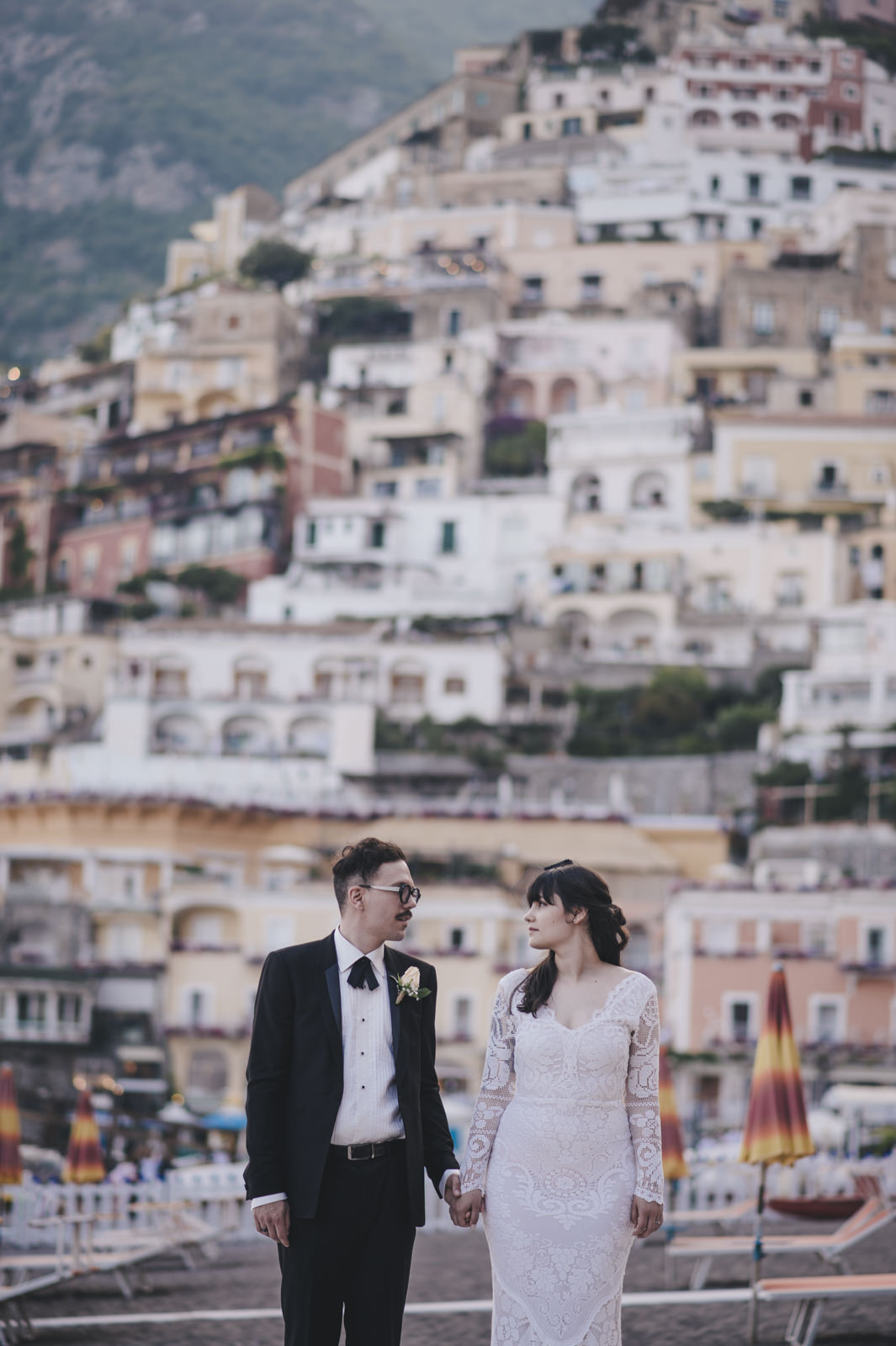 bride and groom's portrait with Positano on the background