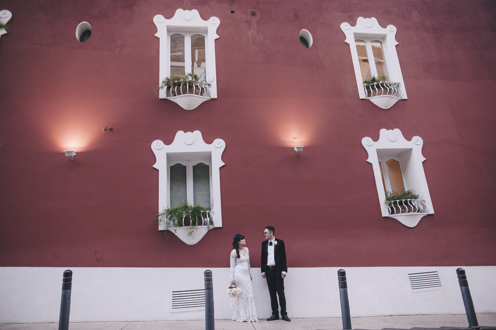 bride and groom's portrait with a red wall on the background