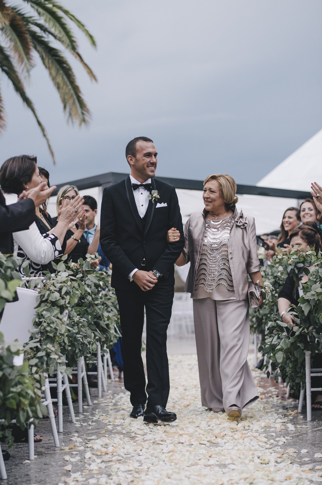 the groom walking down the aisle with his mother
