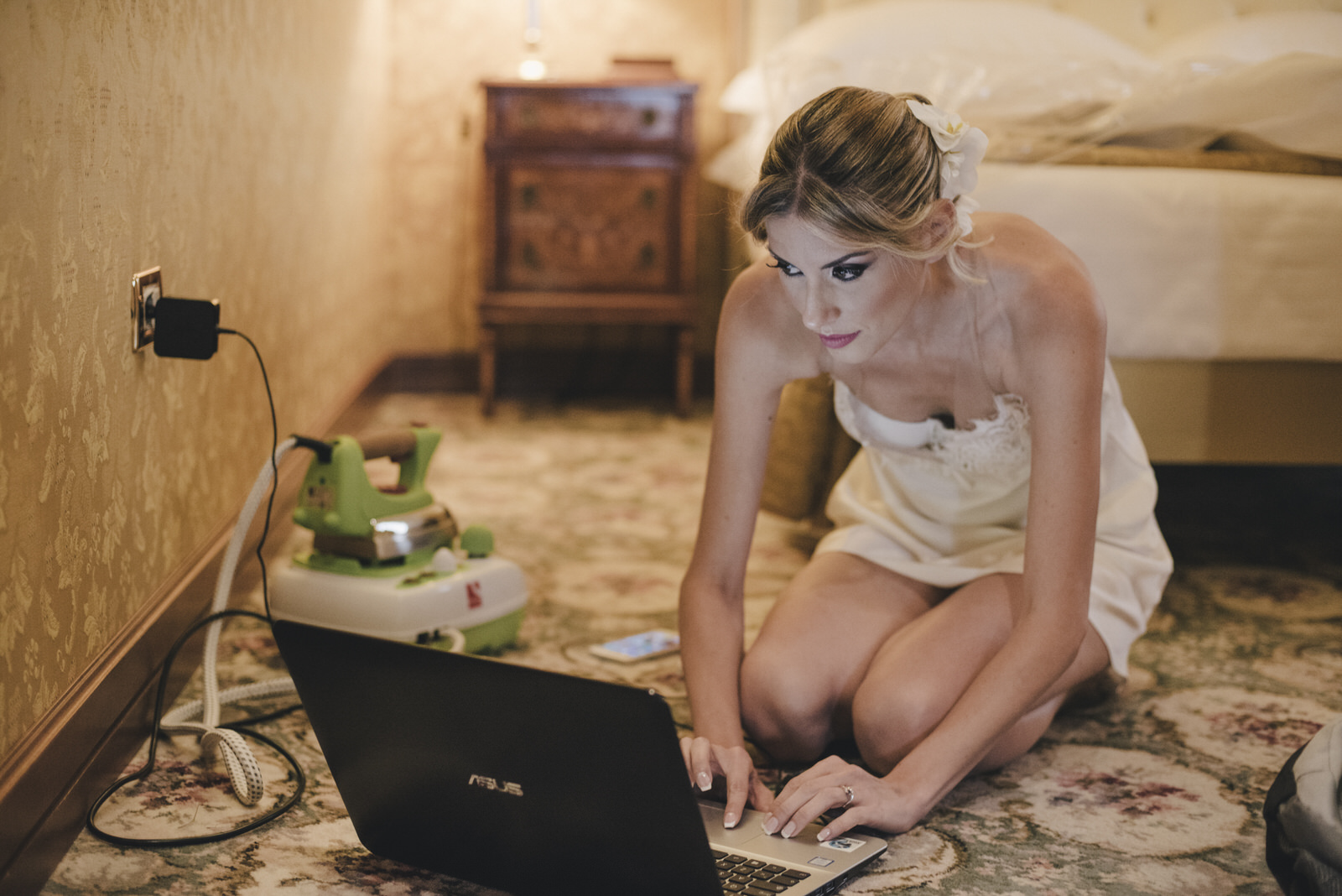 the bride sitting on the floor and writing on her pc