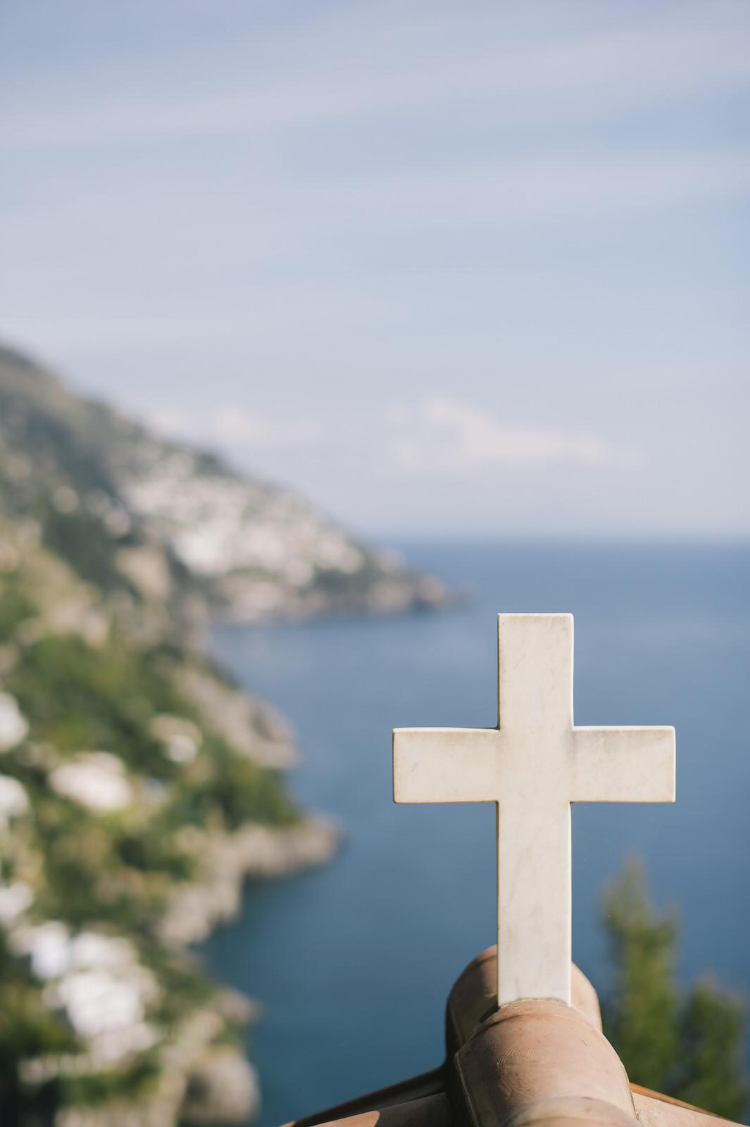 white cross with landscape of amalfi coast
