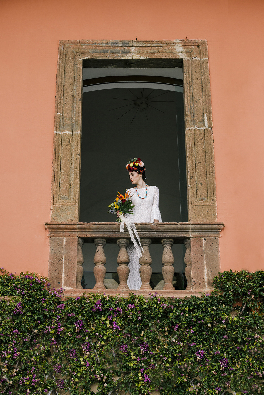 bride's standing on a balcony with her bouquet