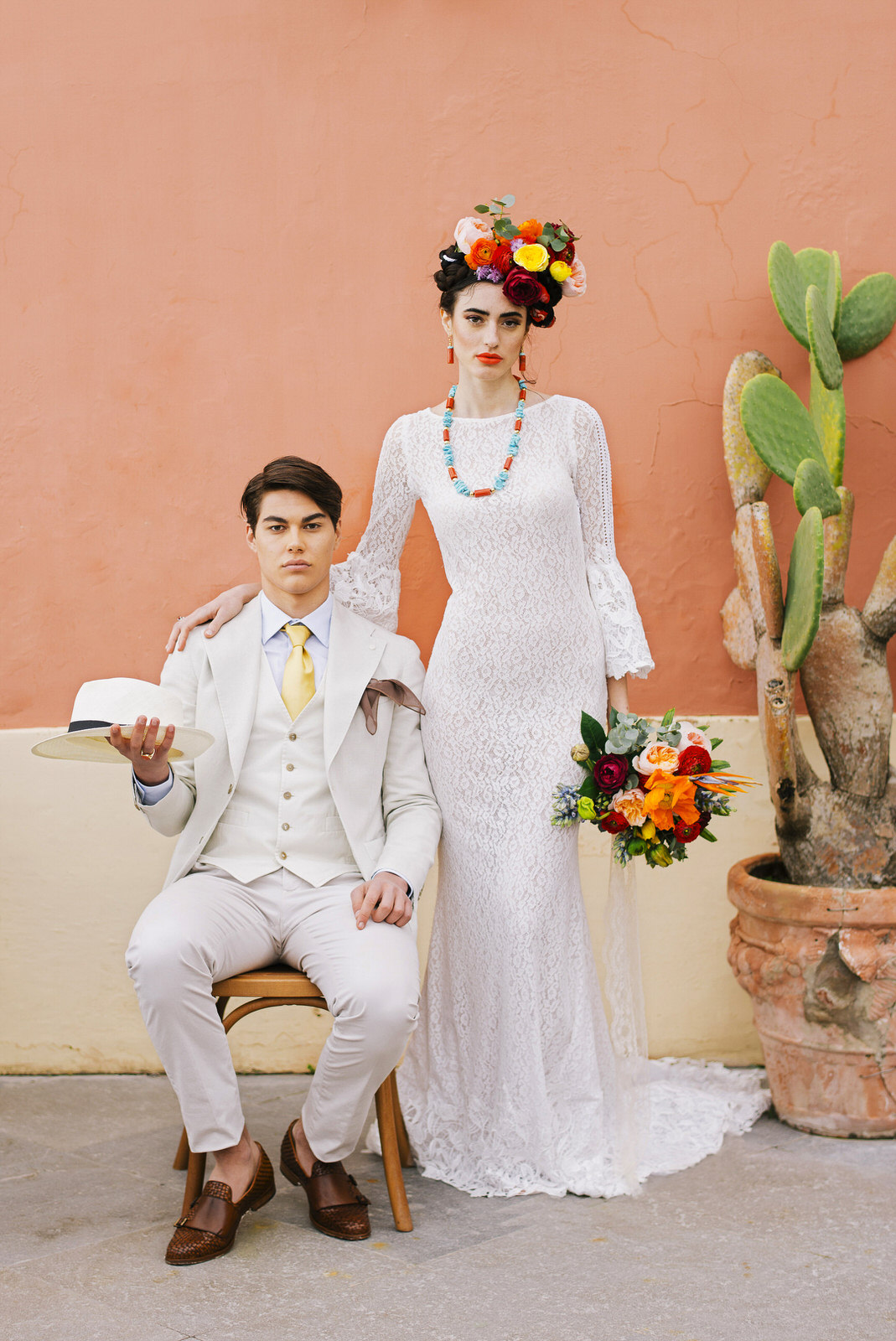 bride and groom's portrait, the groom sitting on the chair and the bride standing